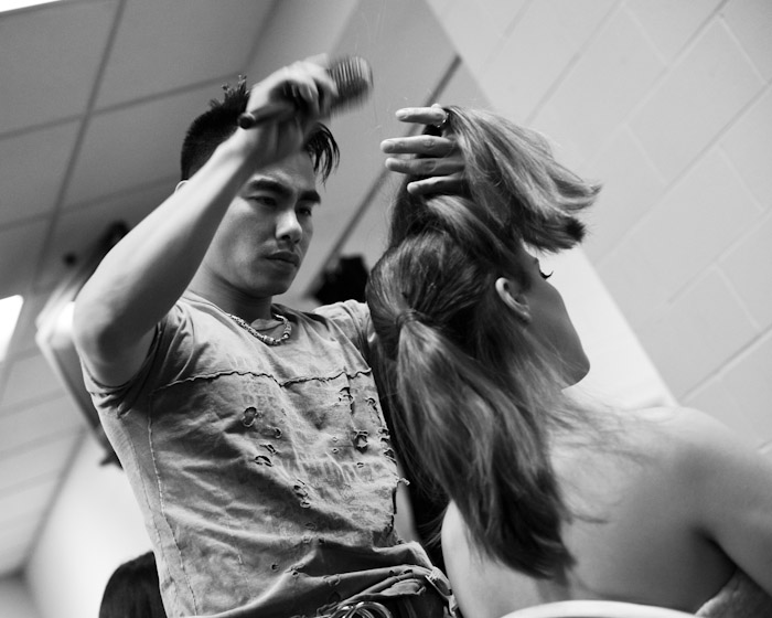 A hairstylist works on one of the models before the show